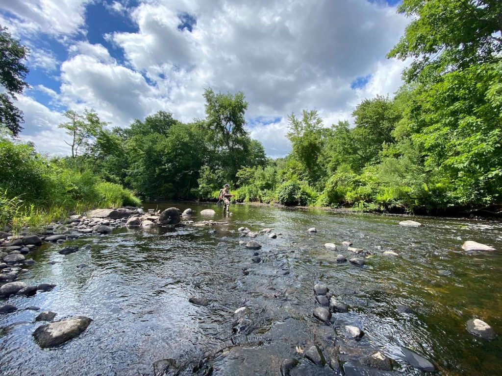 What is Fly Fishing? Fly Fisherman Fishing a Small River