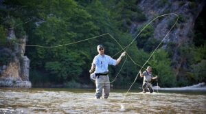 Fly fisher with wading pants in water