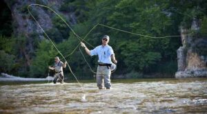 A fly fisherman in the river casting a fly rod