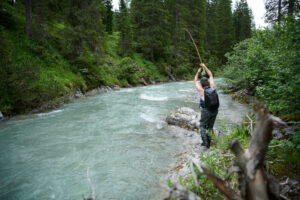 Fly fisherman playing a fish